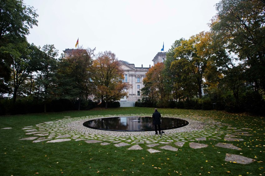 A photographer takes pictures of the Memorial To The Sinti And Roma Murdered Under National Socialism near the Reichstag in Berlin, Germany, Monday, Oct. 22, 2012. The memorial which construction was delayed for about two years will officially open on Wednesday, Oct. 24. (AP Photo/Markus Schreiber)